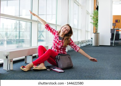 young woman at the airport playing like she can fly