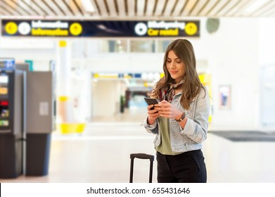 Young woman at the airport with trolley bag, holding a smartphone and texting.