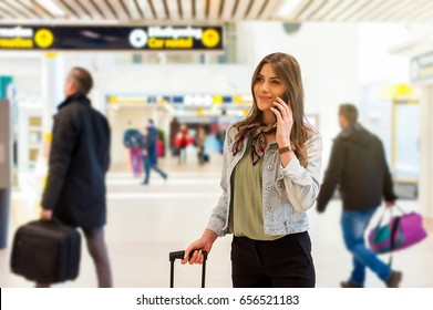 Young woman at the airport with trolley bag, talking on the phone, looking at camera and smiling.