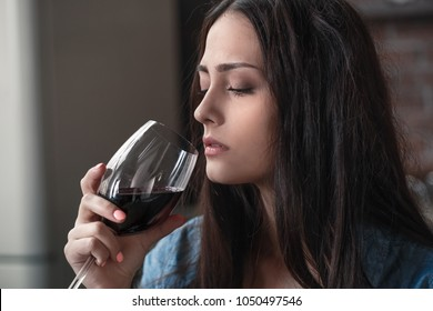 Young woman alcoholic social problems concept sitting drinking wine