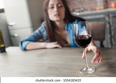 Young woman alcoholic social problems concept sitting reaching glass