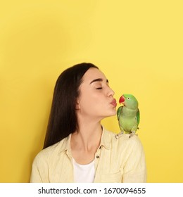 Young woman with Alexandrine parakeet on yellow background, space for text. Cute pet