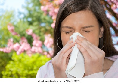 A young woman with a allergy sneezing into handkerchief.