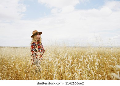 Young woman alone in a field of wheat