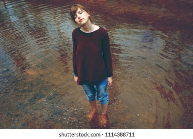 Young woman alone in a lake in an autumn day