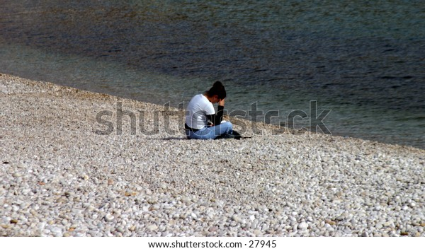 young woman alone on a pebble beach