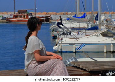young woman alone sitting facing a Mediterranean port, Pyrenees orientales in France