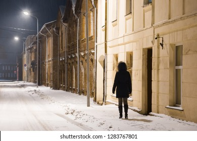 Young woman alone slowly walking on snow covered sidewalk along old houses under white street lights. Dark time. Peaceful atmosphere in night. Back view.