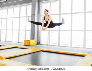 Young woman amateur acrobatic athlete jumping and exercising on a trampoline indoors, modern hobby and fitness concept