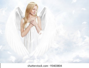 Young woman as angel with white wings and aureole on cloudy background with flying feather