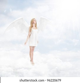 Young woman as angel with white wings standing in a clouds