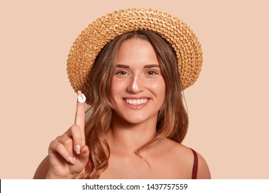 Young woman applaying sunblock on her face, and showinig her finger with sunscreen, model posing isolated over beige background, standing against studio wall with topothy smile, dressed swimming suit.