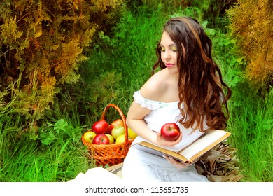 Young Woman with Apple and book in the Orchard. Basket of Apples. Garden
