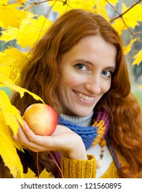 Young woman with apples in the autumn wood among yellow maples