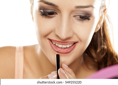 young woman applied contour on her lips with a pencil