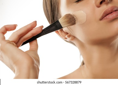 A young woman applied liquid foundation on her face with a brush