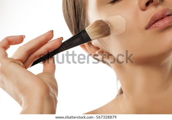 若い女性が、顔に毛で液体の基礎を塗った