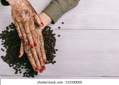 Young woman applies a coffee scrub on hands, top view, copy space