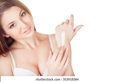 Young woman applies cream on her hands on a white background