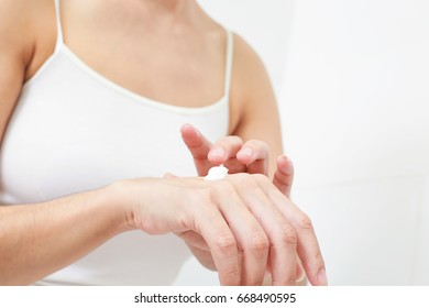 Young woman applies cream on her hands.