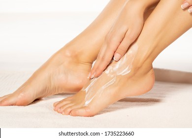 a young woman applies lotion to her feet on white towel