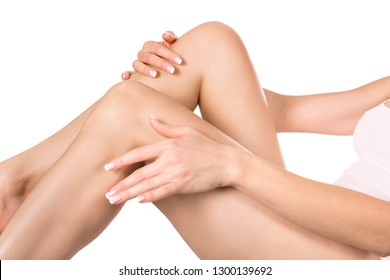 Young woman apply body lotion on her legs. Skin care and health concept