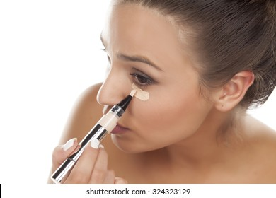 young woman apply concealer under the eye