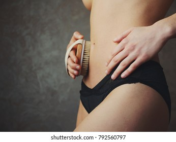young woman apply dry brush on her abdomen