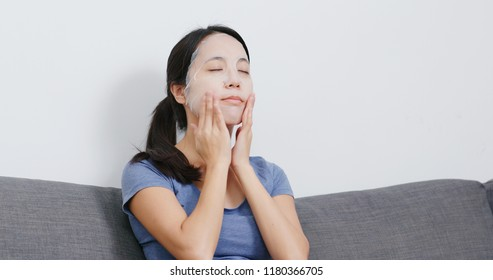 Young Woman apply face mask and sitting on sofa