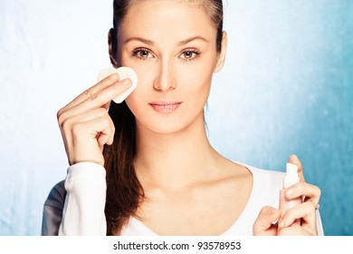 young woman apply foundation with sponge applicator, studio shot