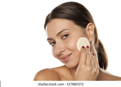young woman apply makeup base on her face