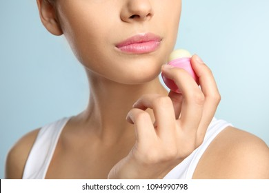 Young woman applying balm on her lips against color background, closeup