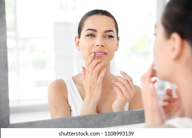 Young woman applying balm on her lips near mirror indoors