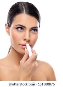 Young woman applying balsam on lips