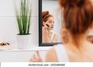 Young woman applying blusher to her cheek in the morning in an over the shoulder view of her reflection in the bathroom mirror
