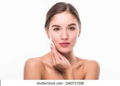 Young woman applying blusher on her face with powder puff isolated on white background