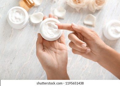 Young woman applying body cream, closeup