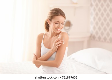 Young woman applying body cream at home - Shutterstock ID 781999633