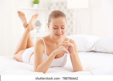 Young woman applying body cream at home