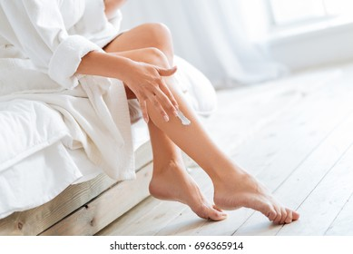 Young woman applying body lotion on legs