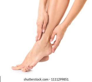 Young woman applying body scrub on feet against white background