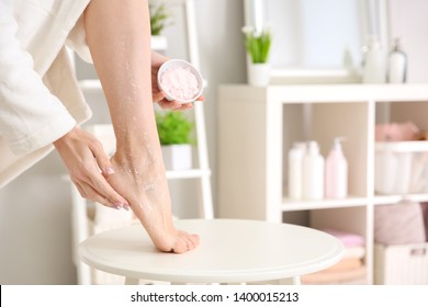 Young woman applying body scrub at home