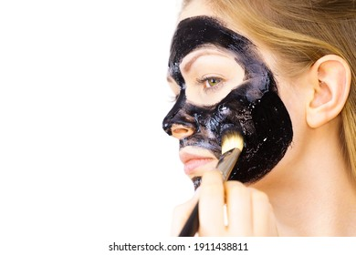 Young woman applying with brush black detox mud mask to her face. Girl taking care of skin. Beauty treatment. Skincare.