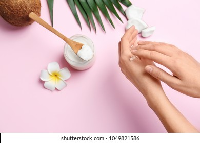 Young woman applying coconut oil on color background, closeup
