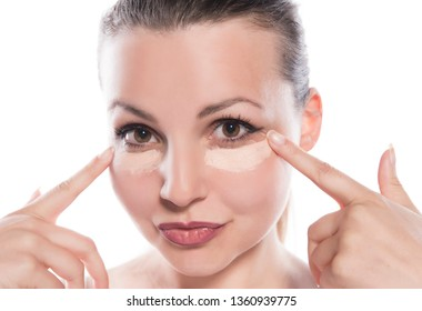 young woman applying concealer on white background