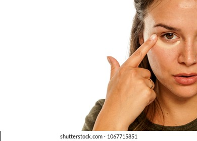 Young woman applying concealer under her eyes on white background