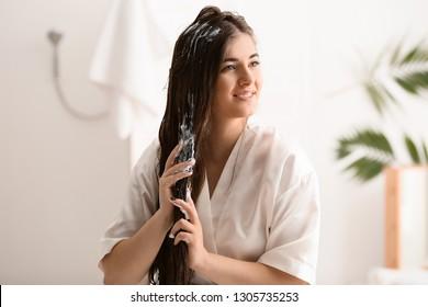 Young woman applying cream on beautiful long hair in bathroom