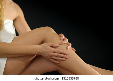 Young woman applying cream on her legs after shaving in bathroom
