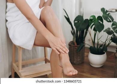 Young woman applying cream on her legs after shaving in bathroom with green plants. Skin care and wellness concept. Girl hand with moisturizer cream smearing legs for soft skin result