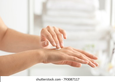 Young woman applying cream on hand against blurred background